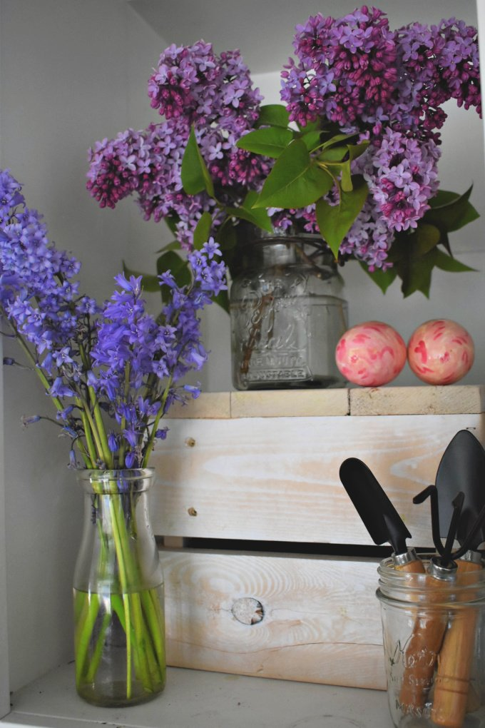 Vases of lilacs and bluebells on a shelf